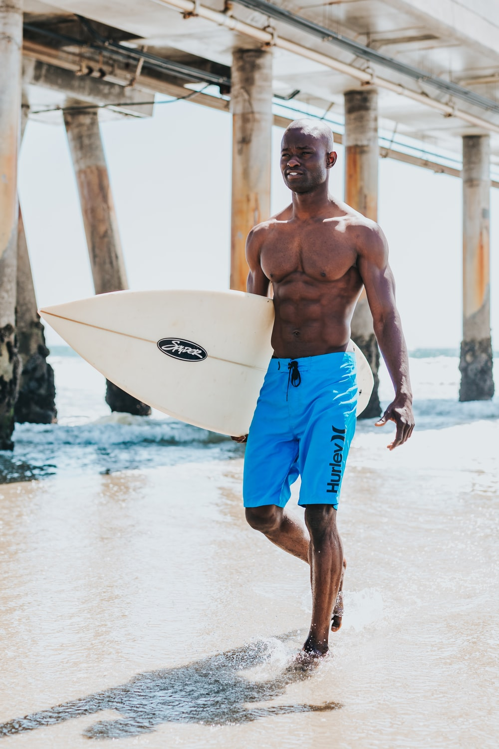man walks on seashore with surfboard during daytime