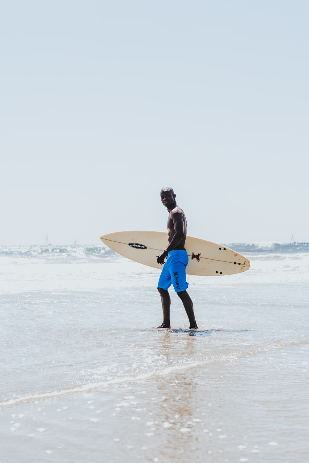 man carrying surfboard standing on shore