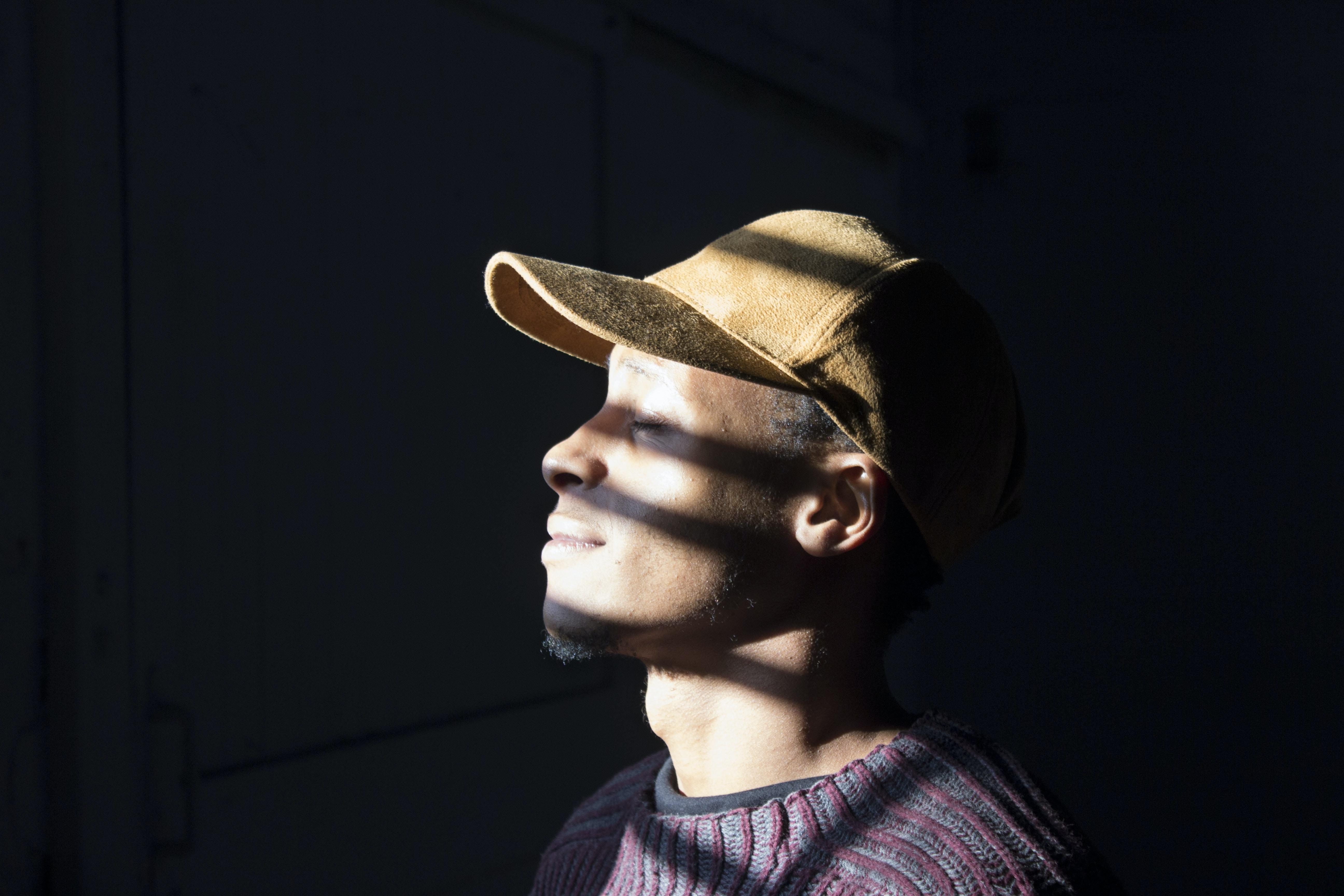 man standing wearing brown cap standing
