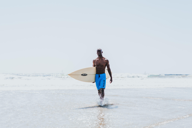 man walking on seashore while holding white surfboard