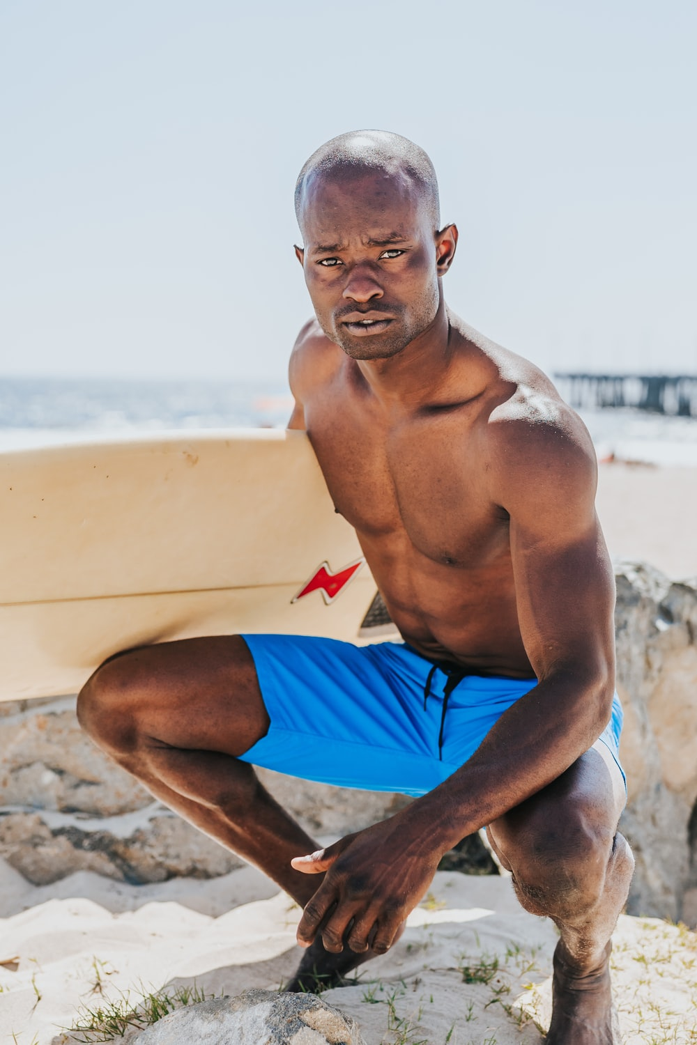 man sitting beside body of water holding white surfing board during daytime