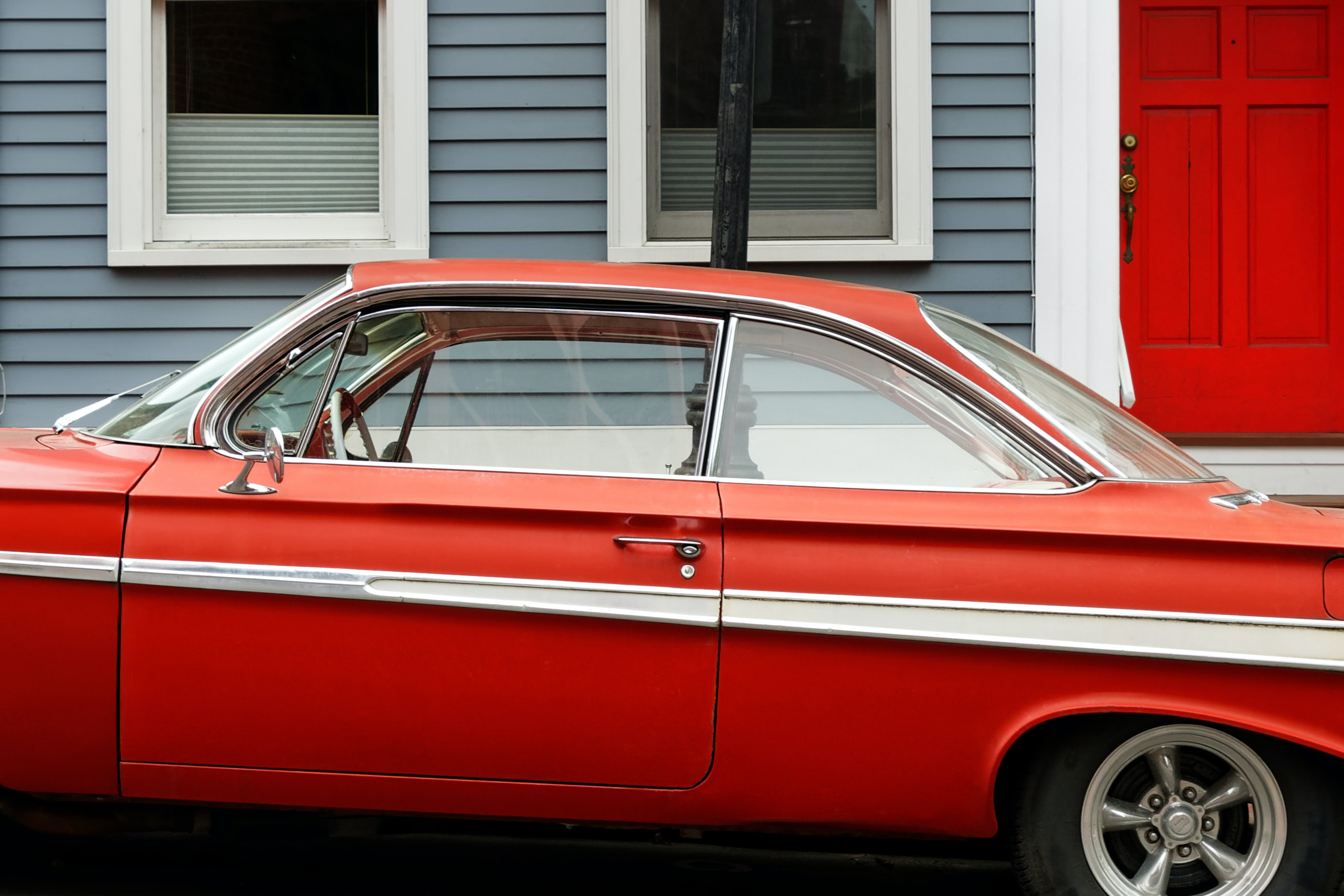 classic red coupe parks beside gray and white wooden house