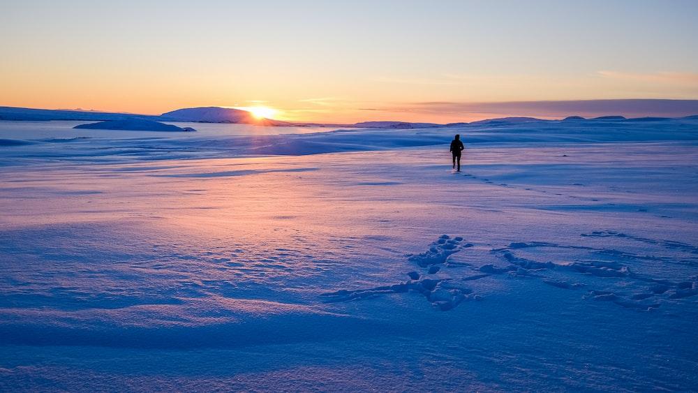man walking on snowfield during sun rise