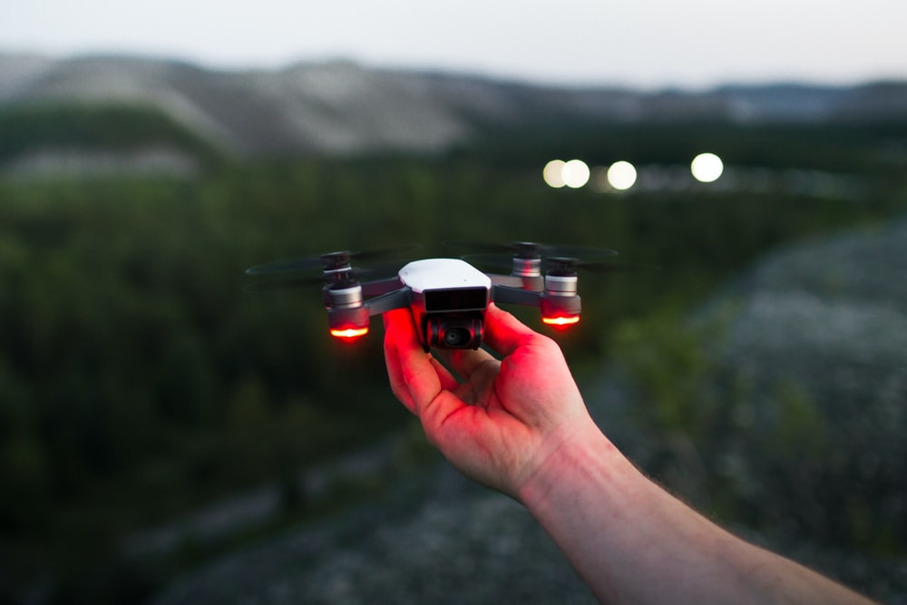 person holding black and red quadcopter