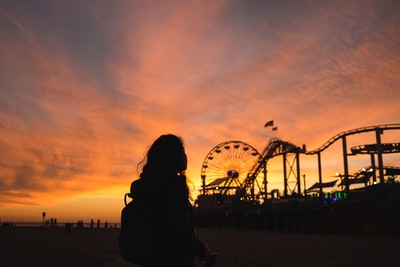 silhouette photography of woman with view of amusement park rollercoaster teams background