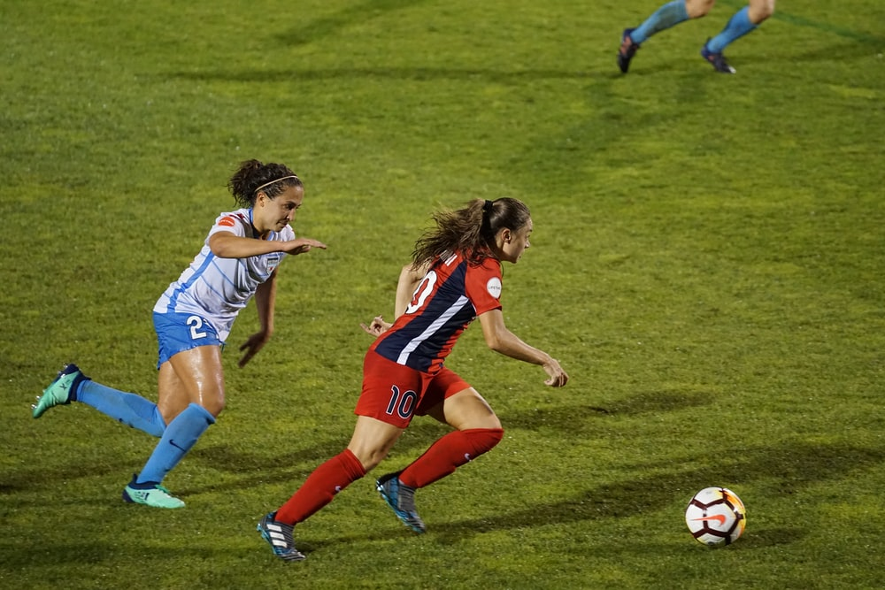 two women playing soccer on field
