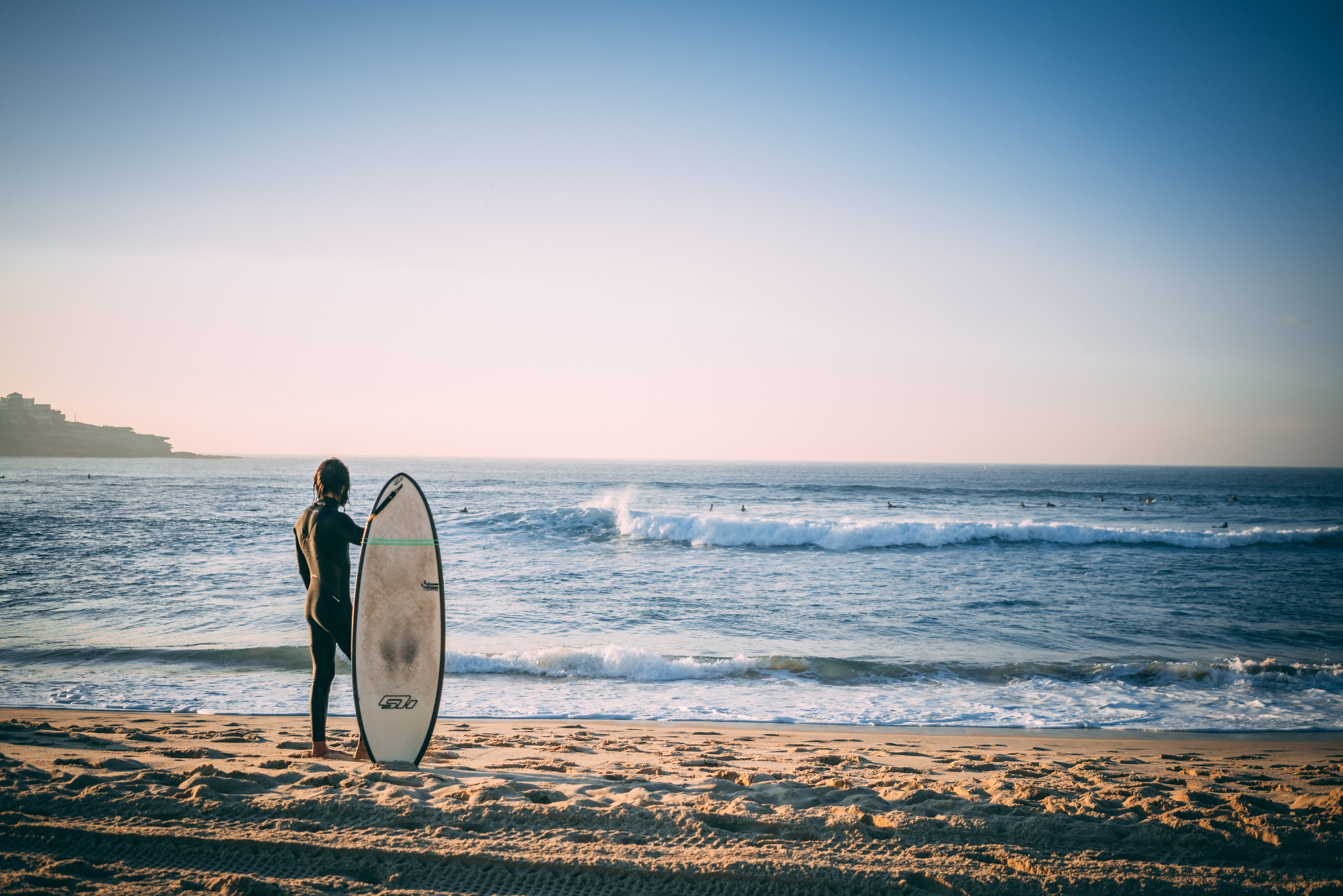 naked person holding surfboard on beach shore