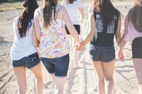 four woman holding hand white walking