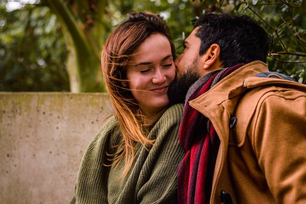 man kissing woman outdoor