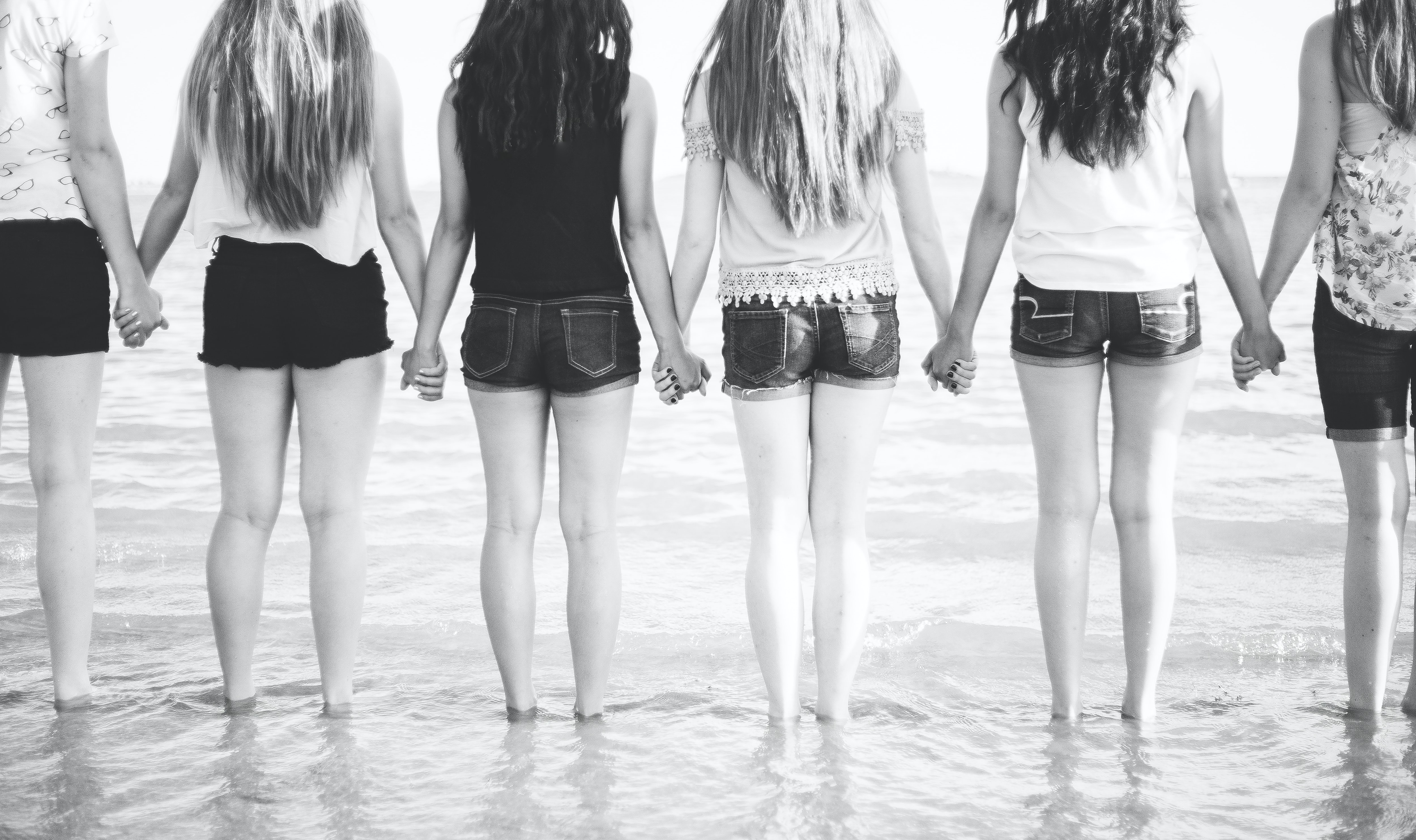group of woman holding hands together on shore