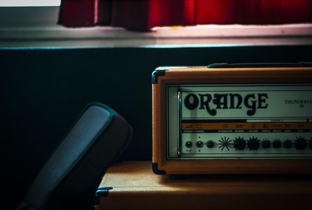 orange and gray Orange radio on brown wooden plank