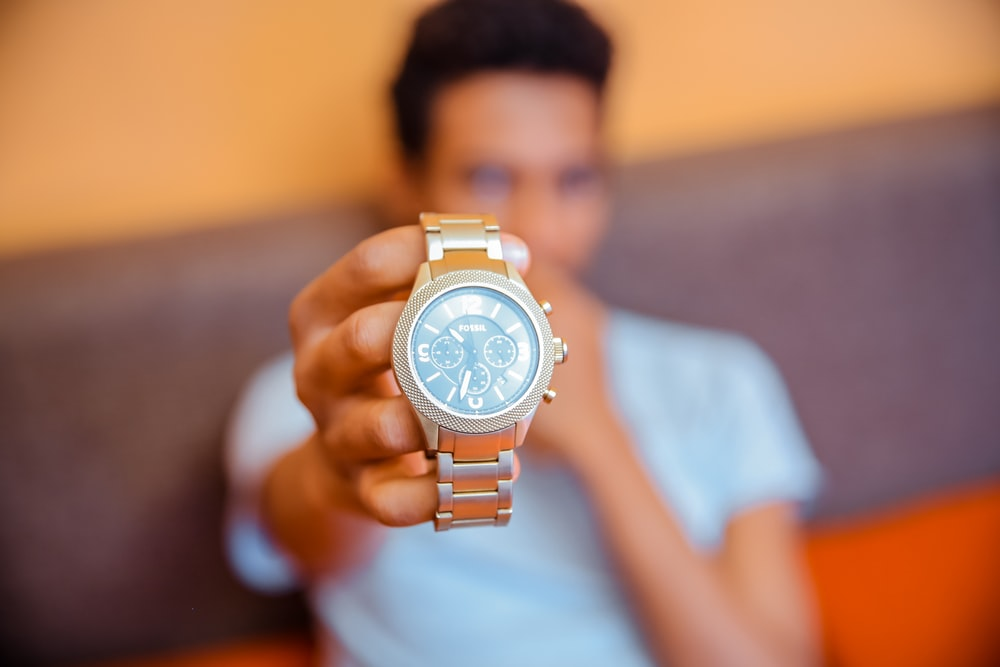 selective focus photography of man holding chronograph watch