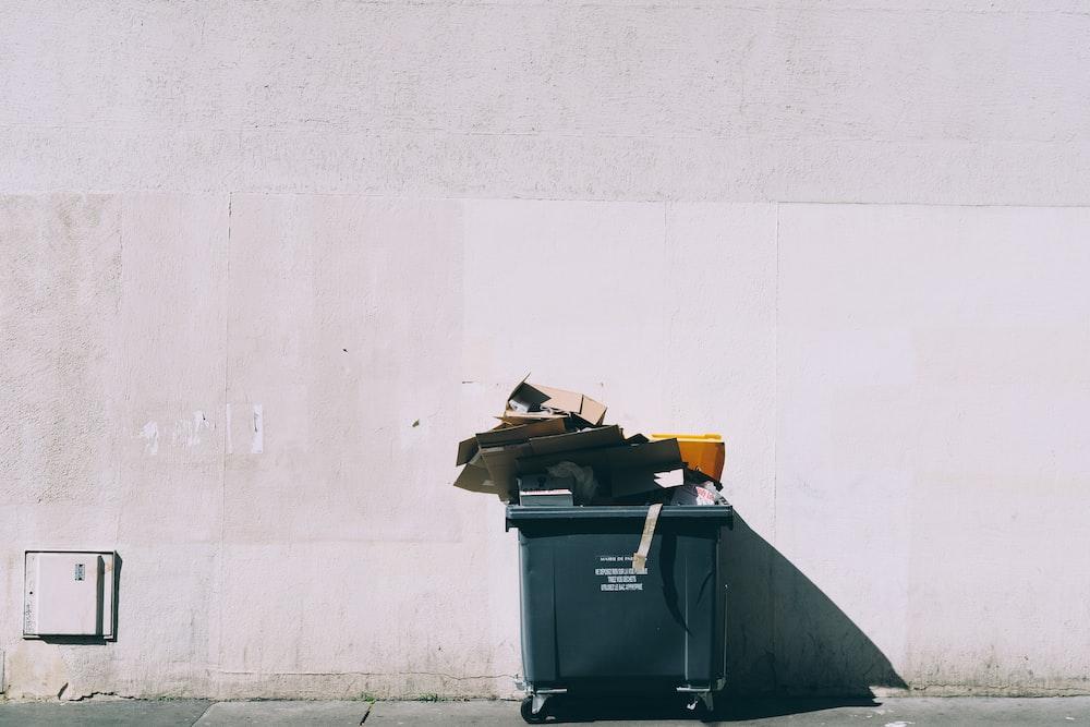 black plastic garbage bin with wheels beside wall