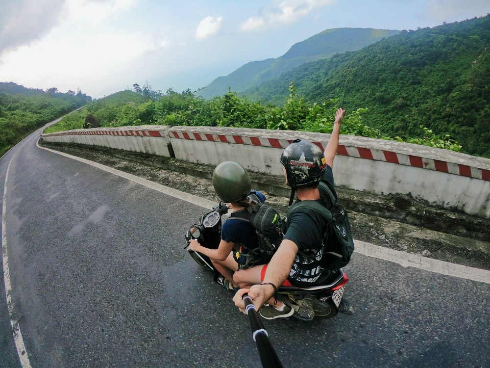 fish eye photography on woman riding motor scooter with man on bridge