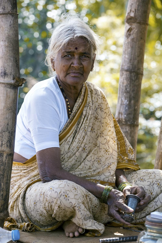 woman sitting beside bamboo tree wearing brown floral shawl