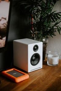 white bookshelf speaker near white candle