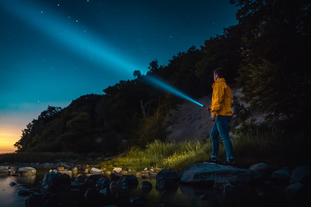 man holding flashlight standing on gray stone during nighttime