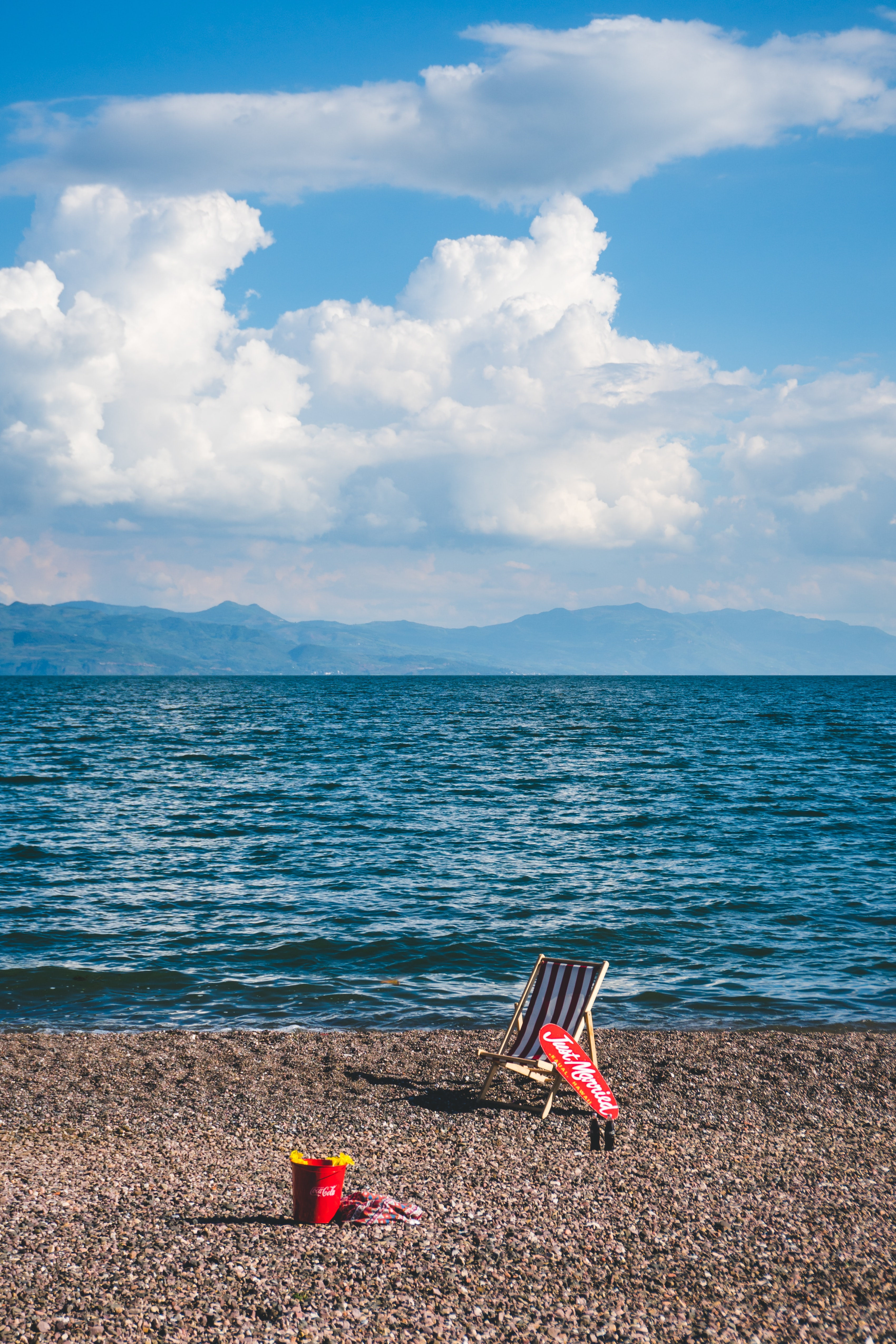 brown wooden camping chair near body of water