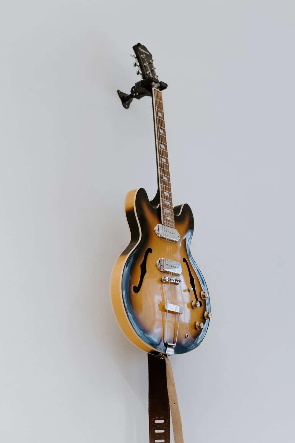 brown electric guitar beside white wall