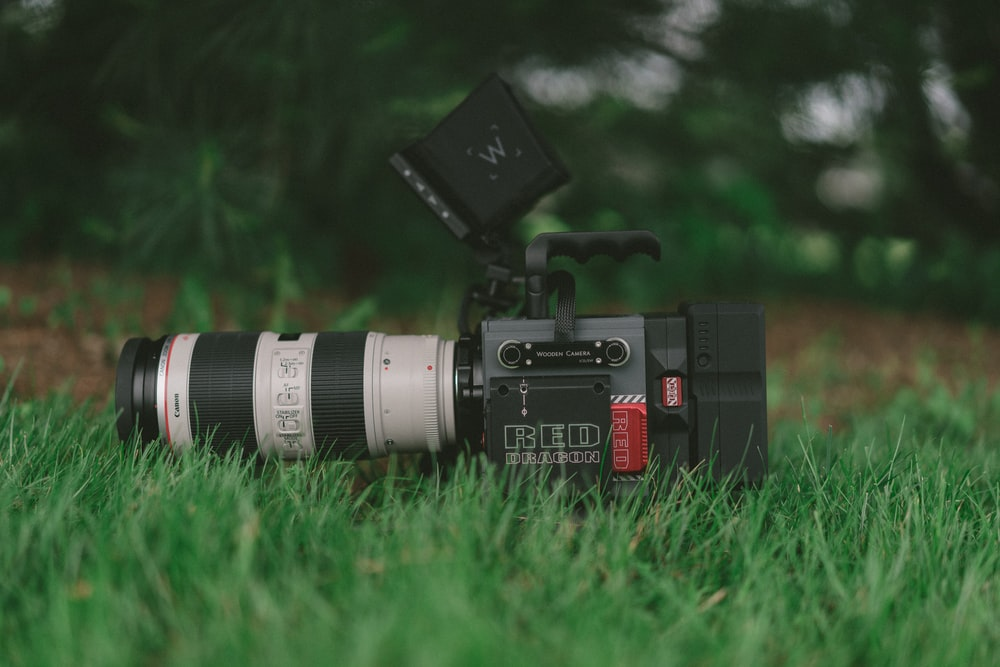 selective focus photography of professional video camera on grass field