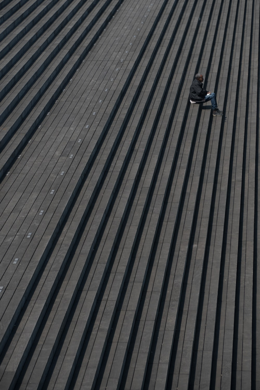 man in black jacket sitting on gray stair