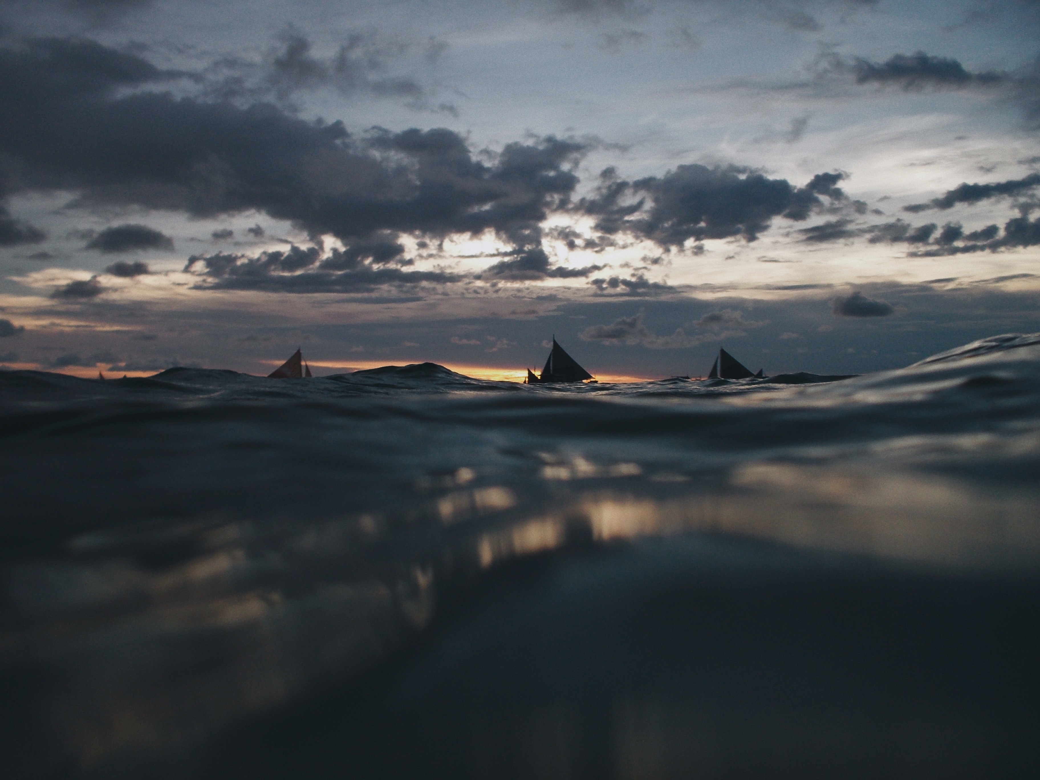 sailboats on body of water under gray clouds