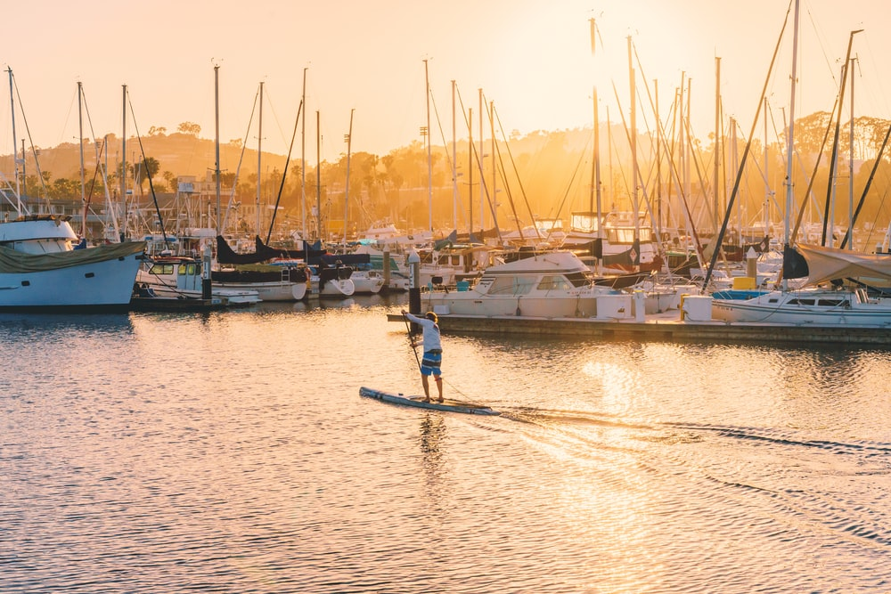 person riding paddle board beside yacht
