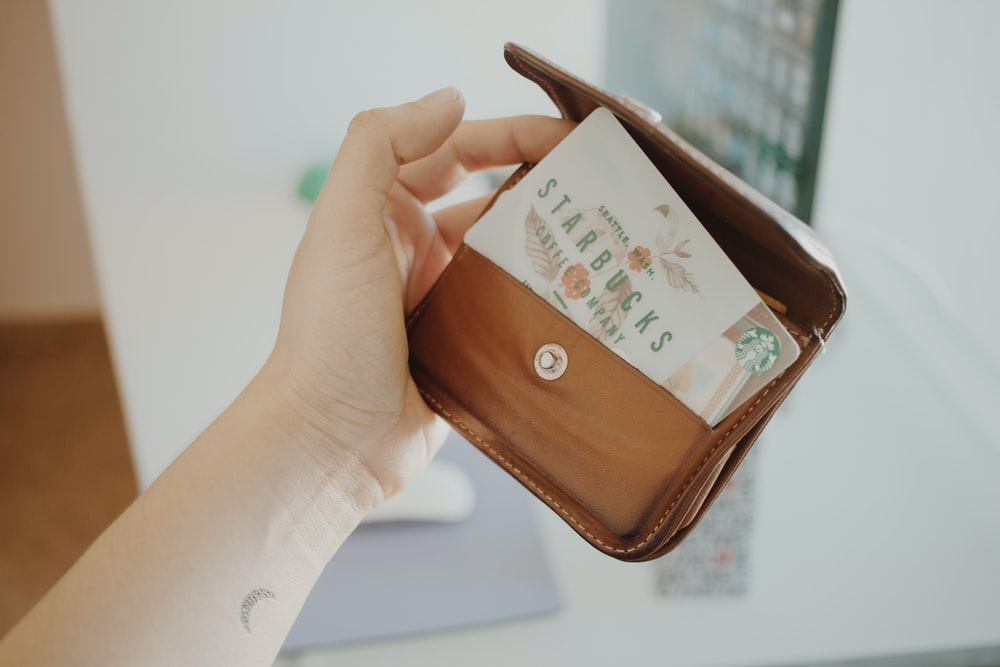 person holding brown leather coin purse