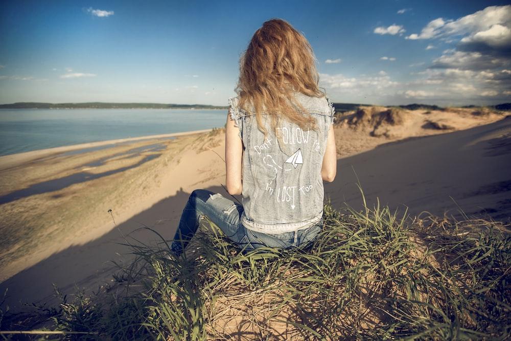 woman sitting on mountain edge