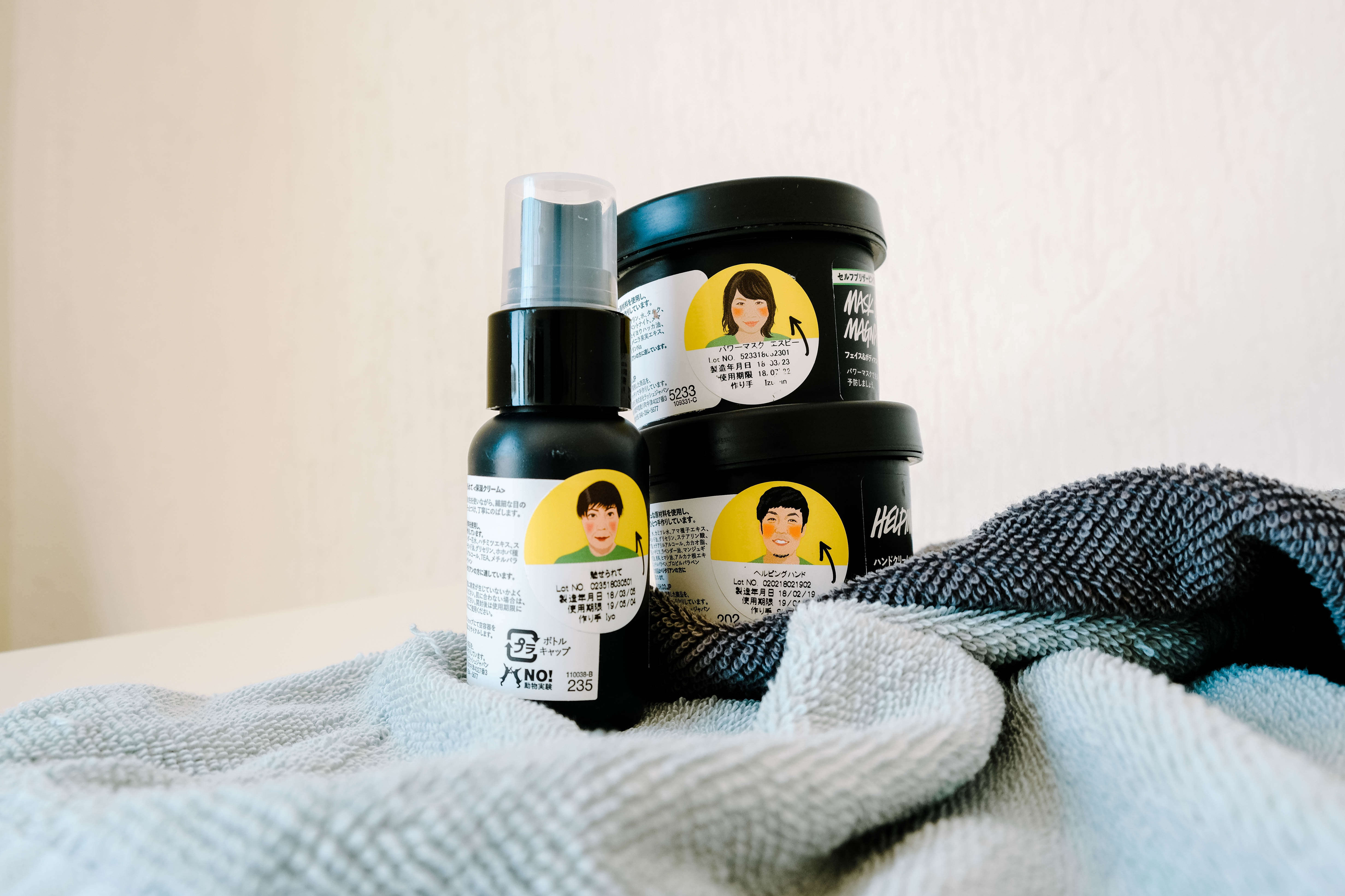 three black and white labeled hair products on white and grey textile