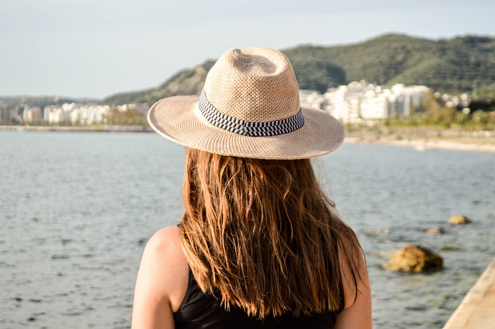 selective focus photography of woman facing body of water