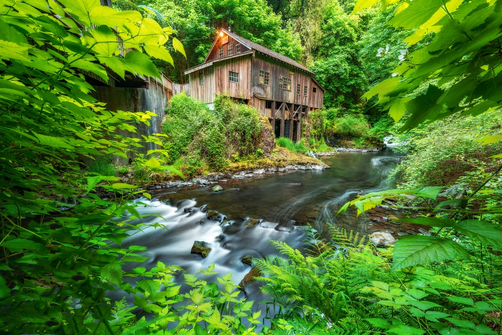 brown wooden house beside body of water