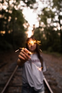 woman holding firecracker standing on train rail surround by trees