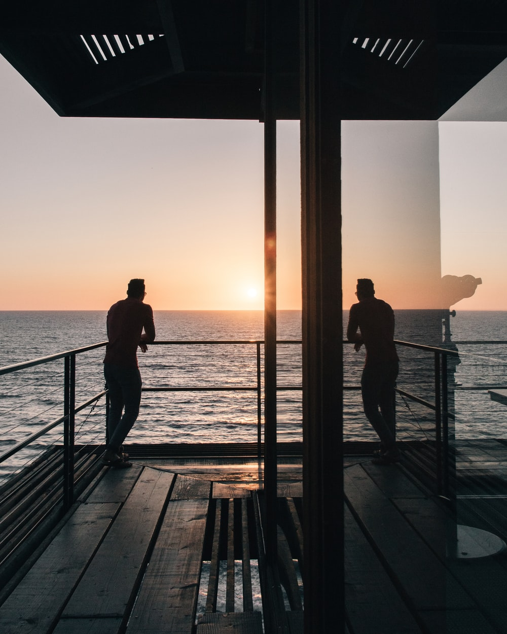 silhouette of man standing on gray stainless steel railing looking at sunset