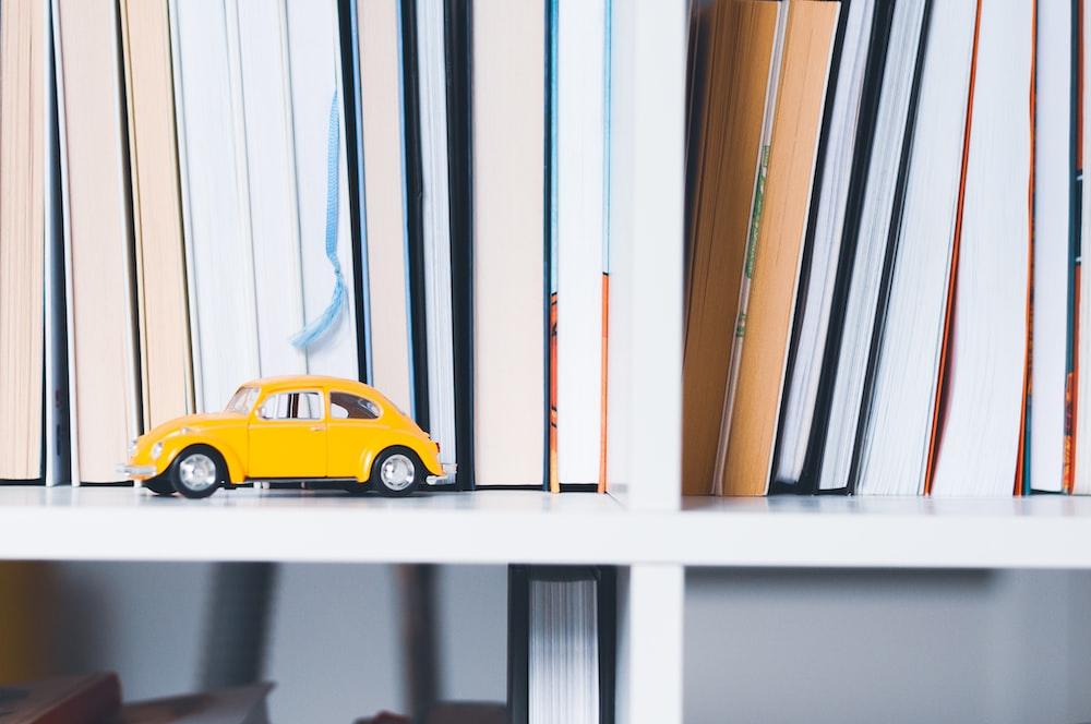 yellow Volkswagen beetle toy on wooden shelf