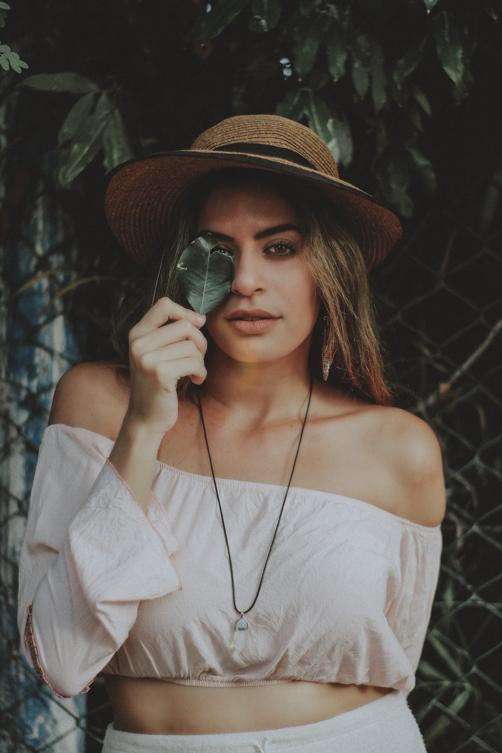 selective focus photography of women in off-shoulder long-sleeved crop shirt holding leaf covering her one eye