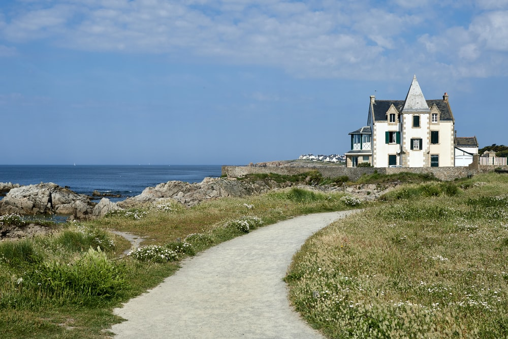 white wooden house near mountain cliff