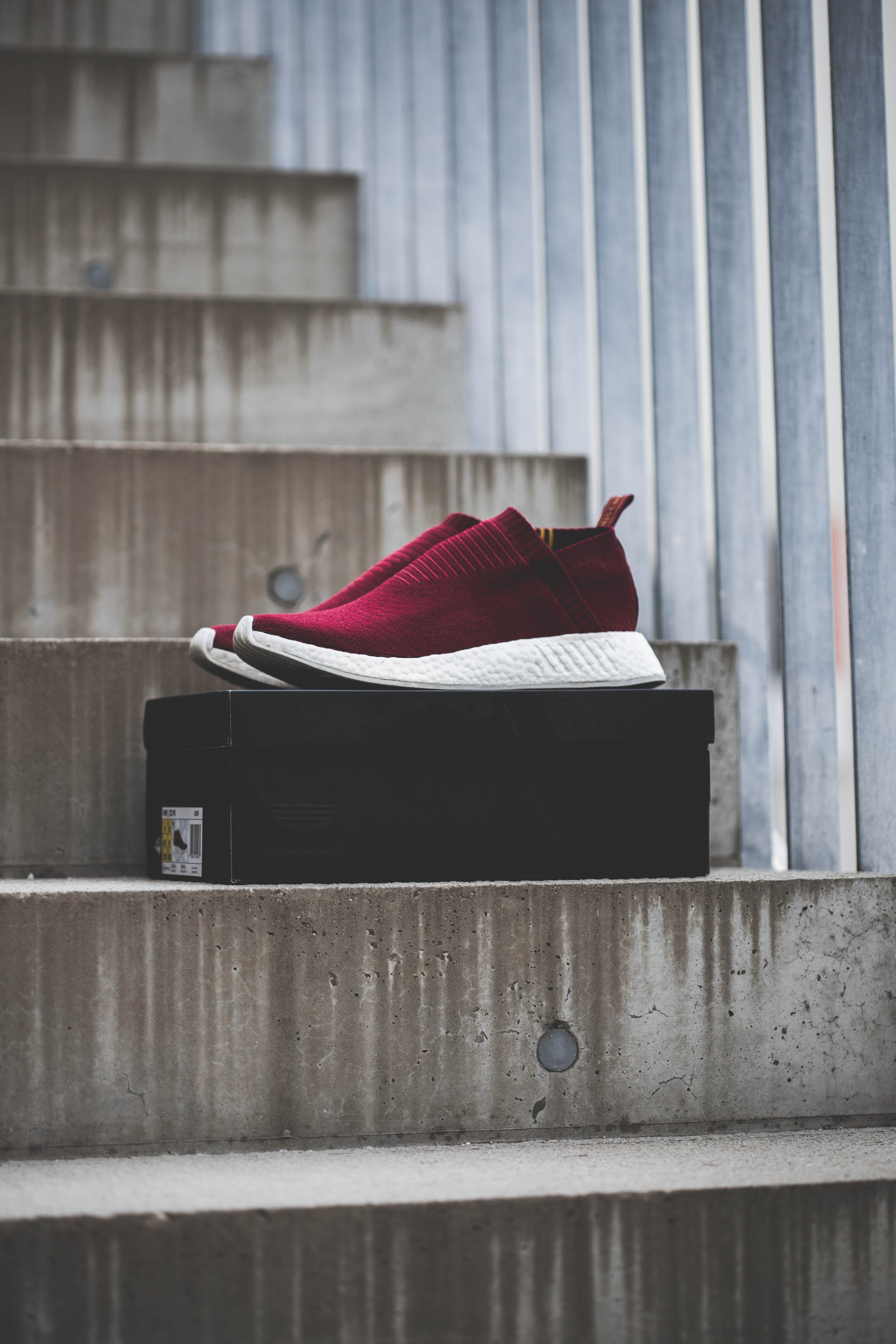 pair of red low-top running shoes with box