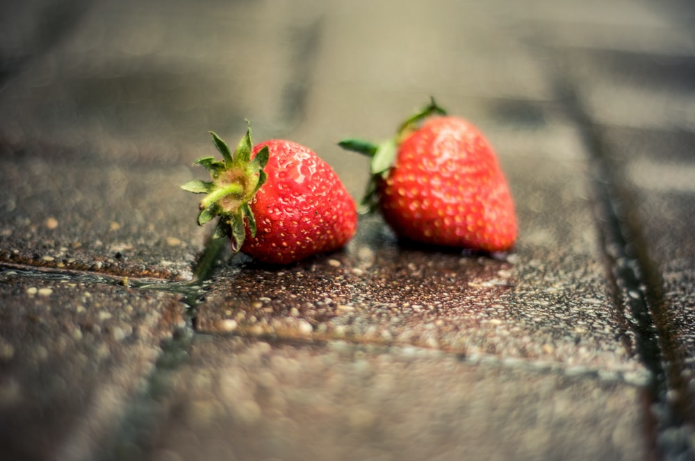 tilt-shift photography of two strawberries on gray brick pavement