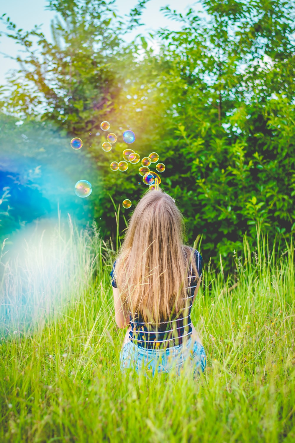 girl sitting while playing bubbles on green grass field near green leaf trees during daytime