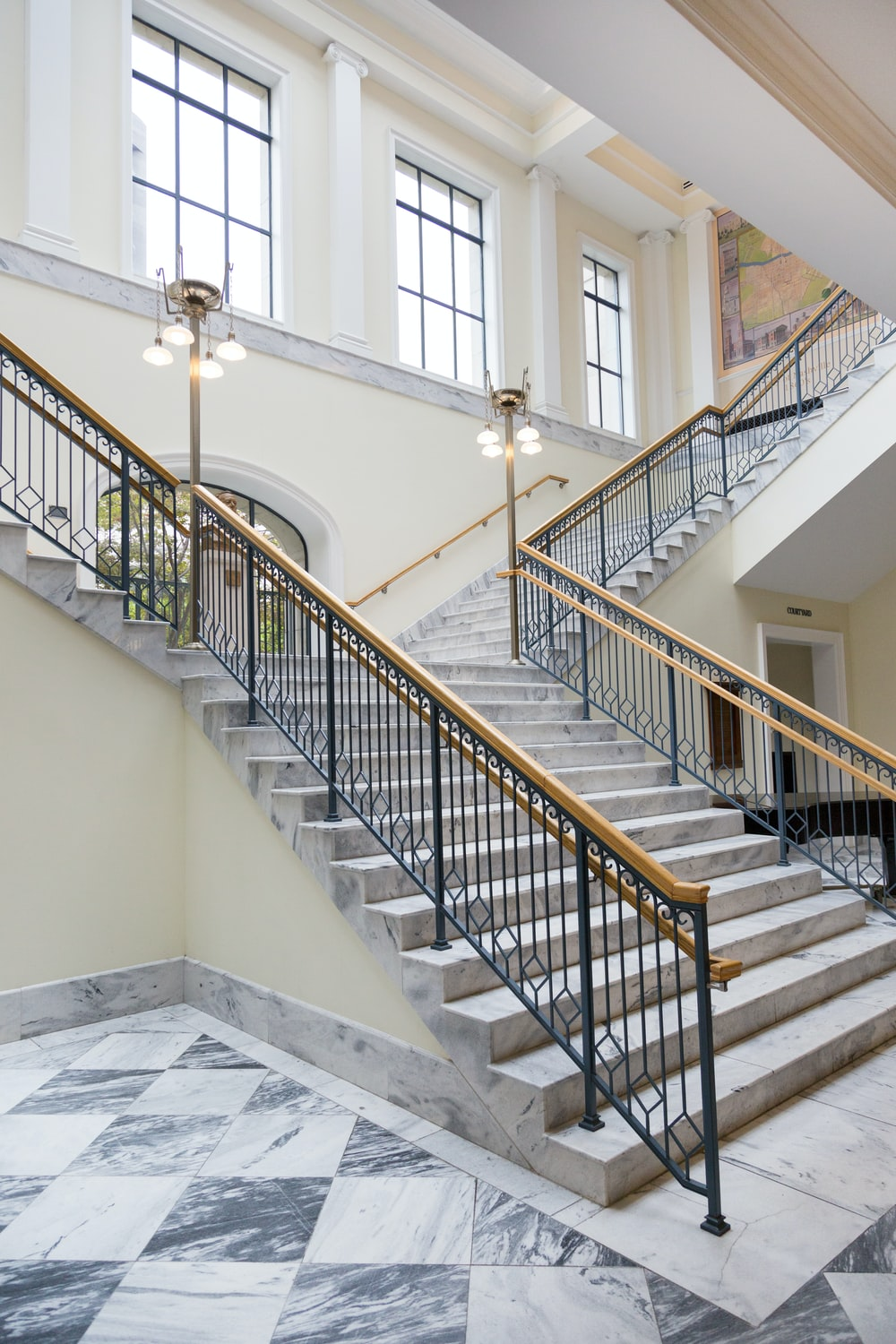 gray and white staircase near window with brass holders
