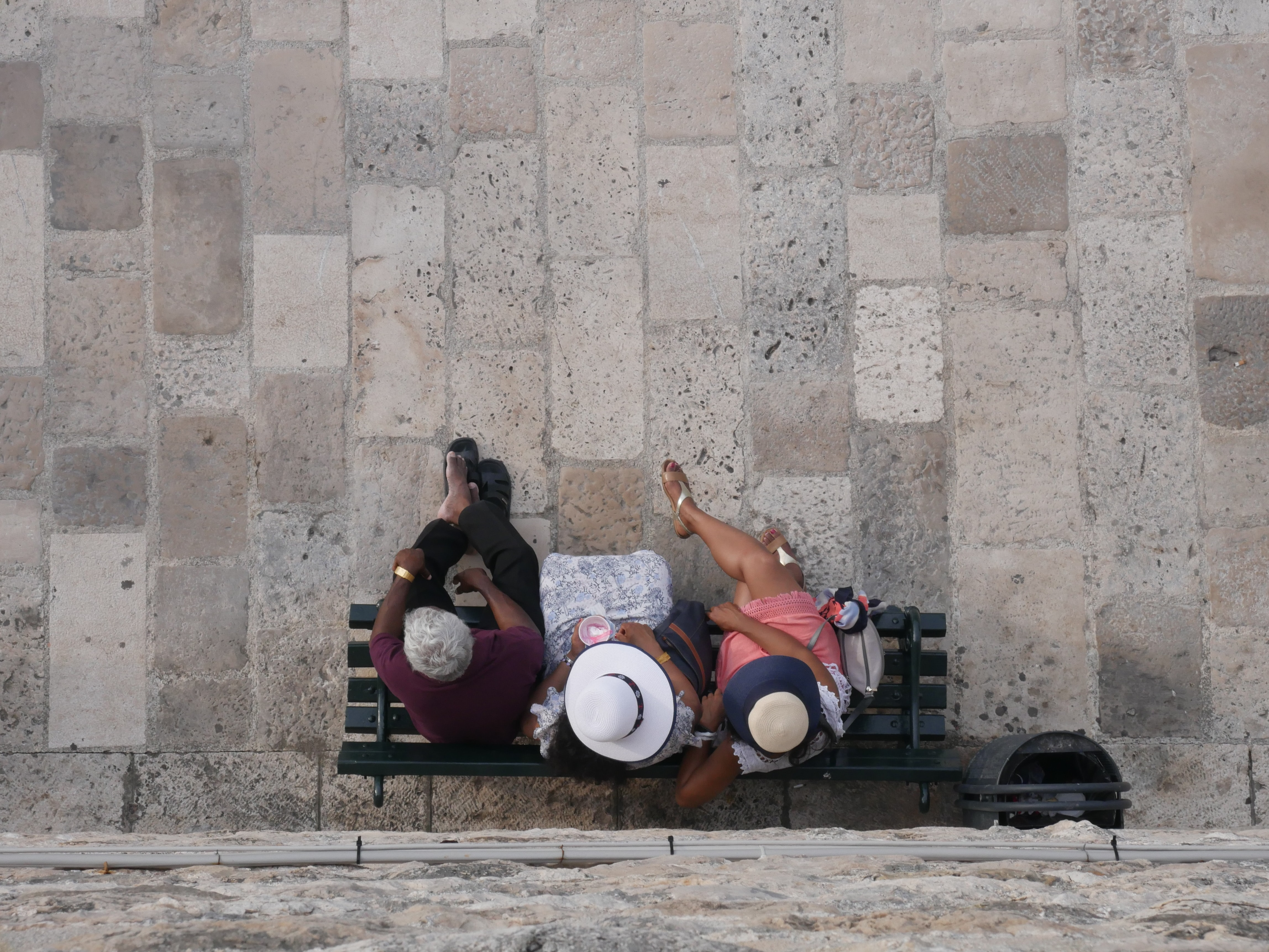 aerial photography of three people sitting on bench