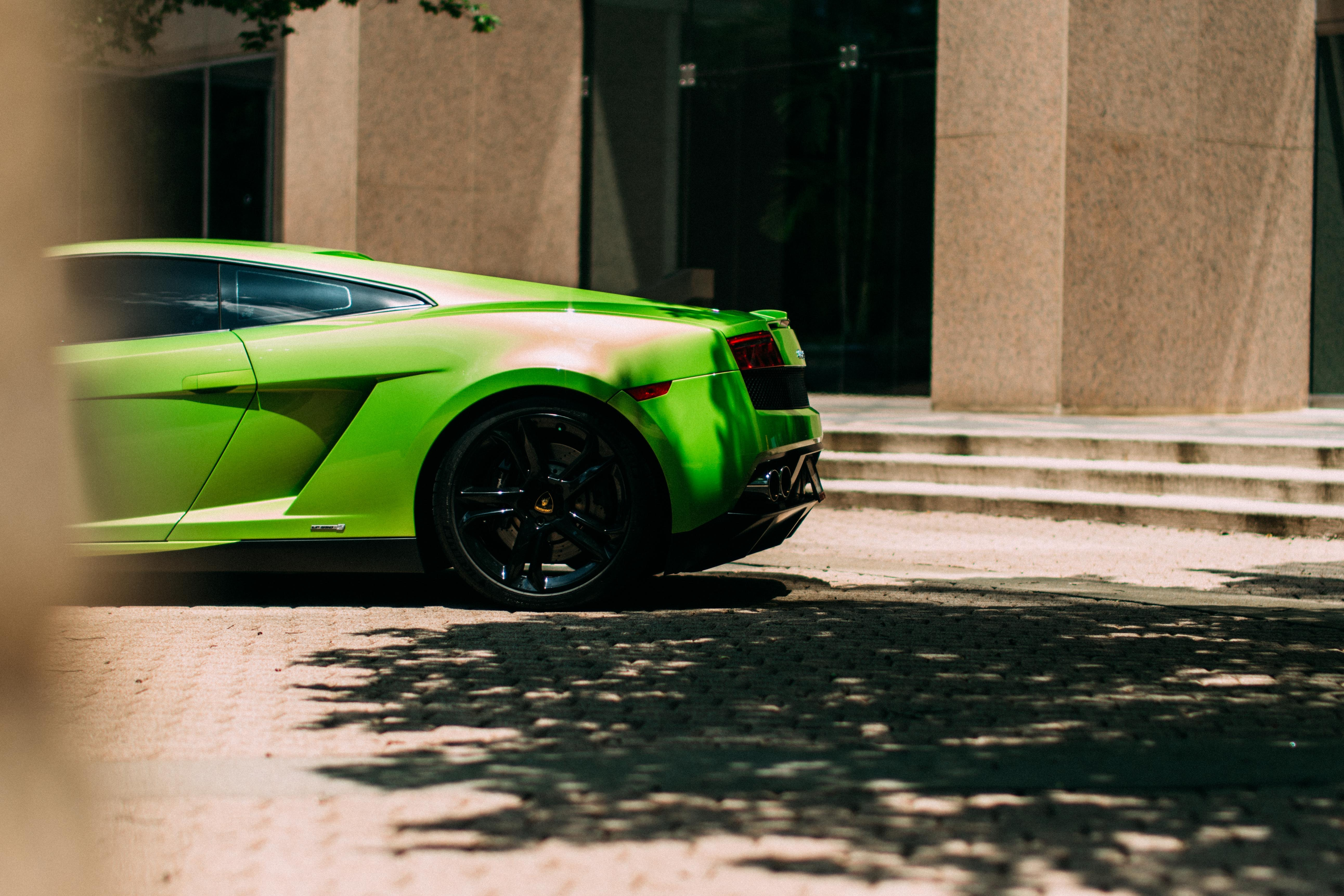 green sports coupe parked at the road near the building