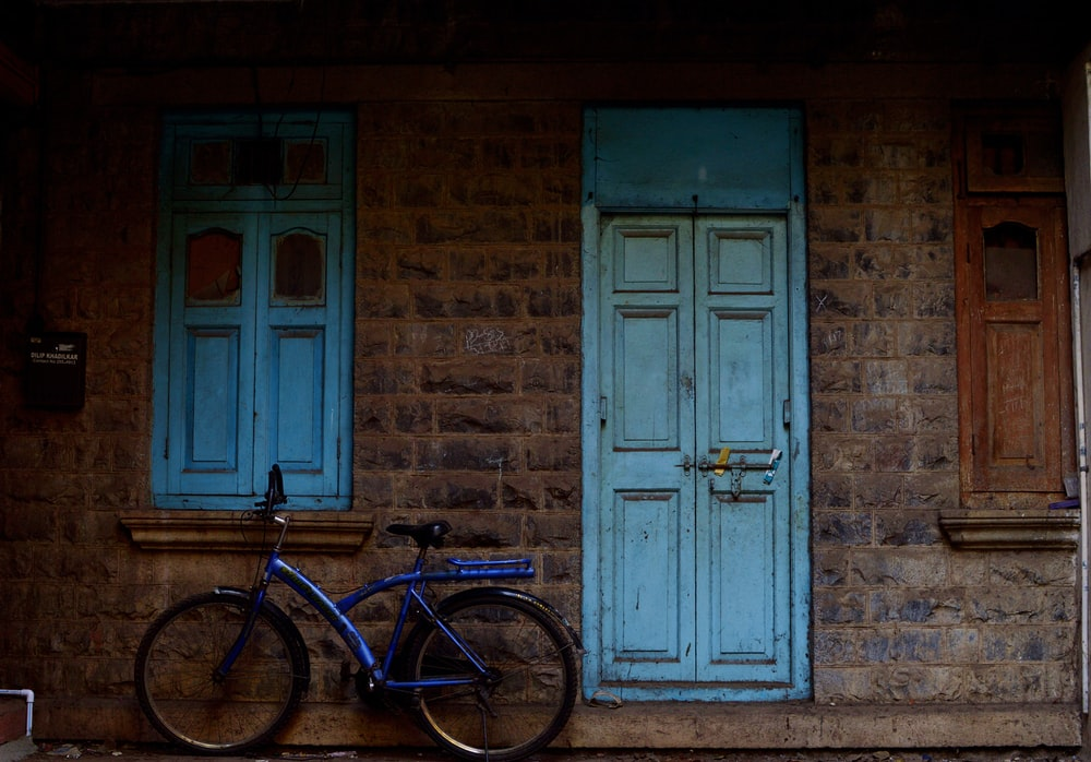 blue bike parked beside building with closed door at daytime