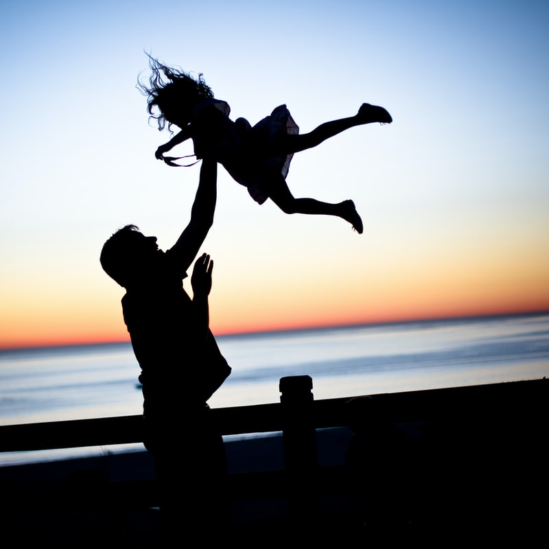 A father playfully tossing his daughter into the air as the sun sets