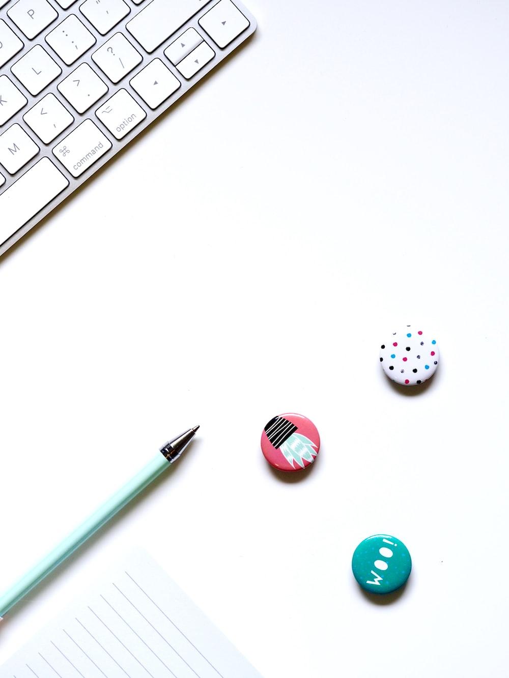 thre assorted button pins near green ballpoint pen