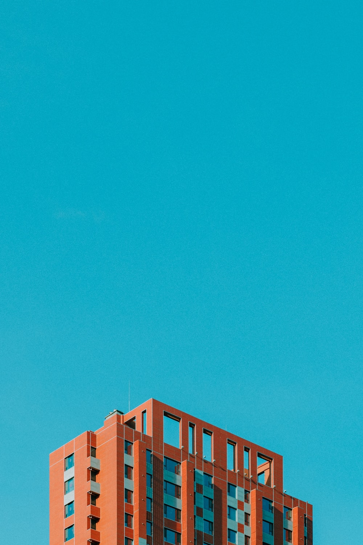 brown high-rise concrete building under blue sky