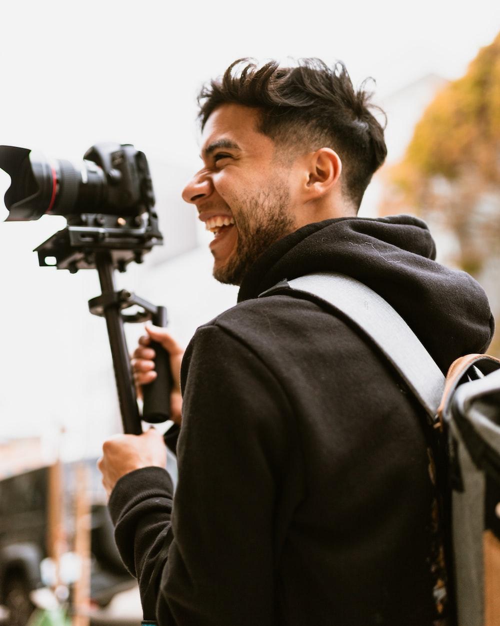 man smiling while holding DSLR camera