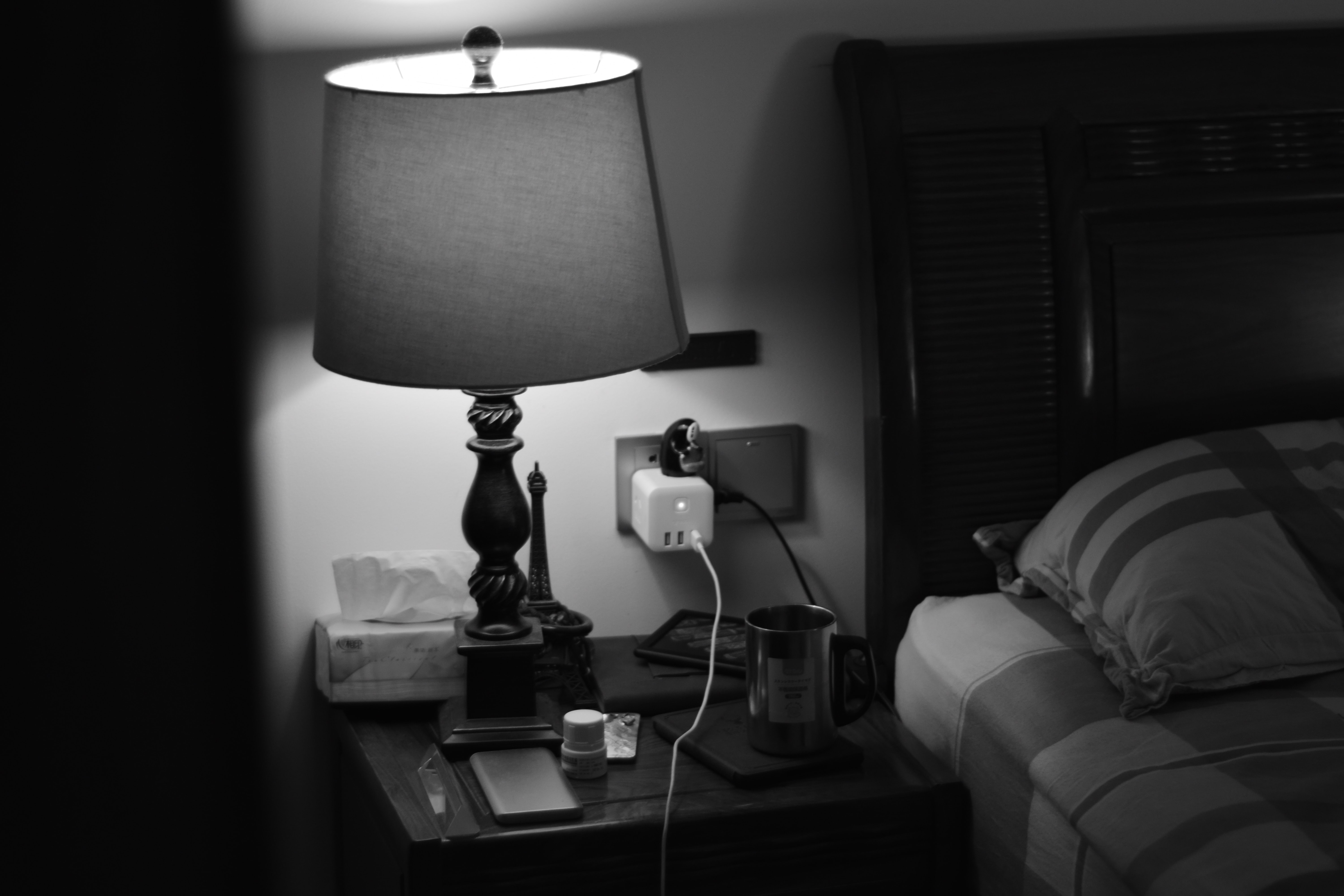 grayscale photo of table lamp near bead