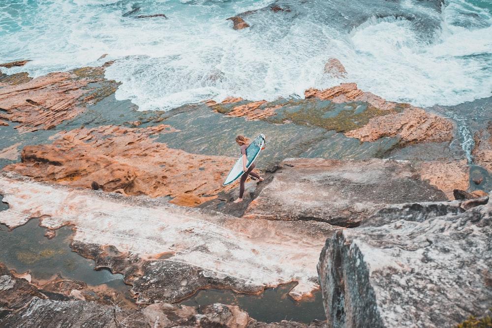 person holding surfboard on seashore